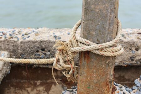tied knot: Old fishing boat rope with a Tied Knot around the old concrete post