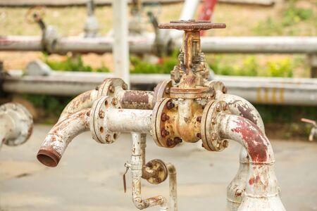 tanque de combustible: Tubos met�licos oxidados y v�lvulas de mano en estaci�n de tanque de combustible Foto de archivo