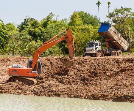 earthmover: SATTAHIP , THAILAND – JULY 25, 2015 : Backhoe and truck on the construction at digging the pit. Preparatory work for the construction of grain silos. The work of construction machinery in a quarry , Thailand on July 25, 2015 Editorial