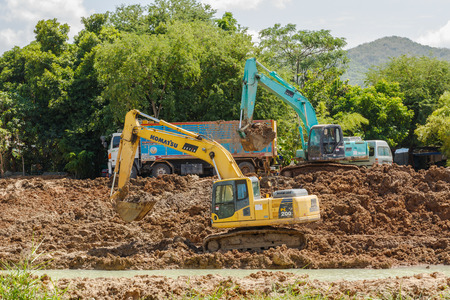 preparatory: SATTAHIP , THAILAND - AUGUST 5, 2015 : Backhoe and truck on the construction at digging the pit. Preparatory work for the construction of grain silos. The work of construction machinery in a quarry , Thailand on August 5, 2015