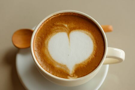 silhouette coeur: Heart shape in hot cappuccino coffee cup on white desk Banque d'images