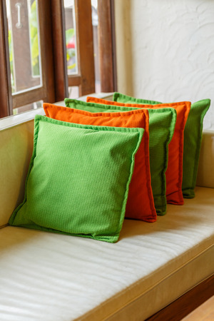 red sofa: Green and red  Decorative pillows on white leather sofa Stock Photo