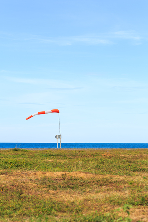 wind force: a wind force (windsock) against the dark sea and blue sky