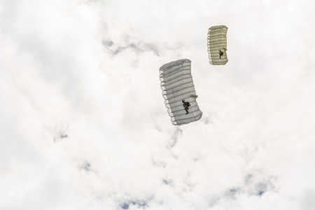 descends: Parachutist descends and trains in landing accuracy that parachute fly on sky with white cloud in day Stock Photo
