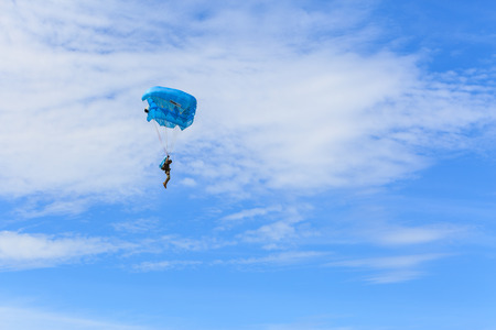 descends: SATTAHIP , THAILAND – SEPTEMBER 11 , 2015 : The parachutist descends and trains in landing accuracy that parachute fly on blue sky with white cloud in day in Sattahip ,  Thailand on September 11 ,2015