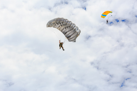 descends: SATTAHIP , THAILAND – SEPTEMBER 10 , 2015 : The parachutist descends and trains in landing accuracy that parachute fly on blue sky with white cloud in day in Sattahip ,  Thailand on September 10 ,2015 Editorial