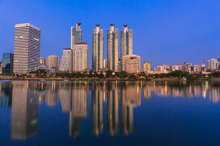 benjakitti: BANGKOK, THAILAND-NOVEMBER 28 : The business skyscraper skyline are in Bangkok city downtown with reflection on wide lake in twilight time in Bangkok, Thailand on November 28,2015