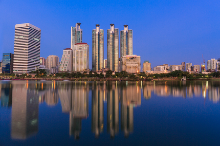 benjakitti: BANGKOK, THAILAND-NOVEMBER 23 : The business skyscraper skyline are in Bangkok city downtown with reflection on wide lake in twilight time in Bangkok, Thailand on November 23,2015
