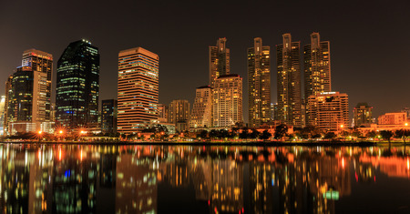 benjakitti: BANGKOK, THAILAND-NOVEMBER 28 : The business skyscraper skyline are in Bangkok city downtown with reflection on wide lake in night time in Bangkok, Thailand on November 28,2015
