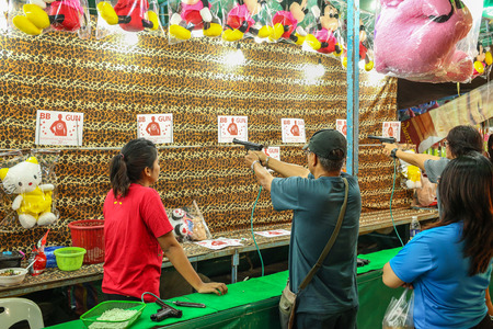 bb: BANGKOK ,THAILAND – DECEMBER 15, 2014: A view of a man shooting  BB gun at Temple fair in Bangkok , Thailand on December 15, 2015