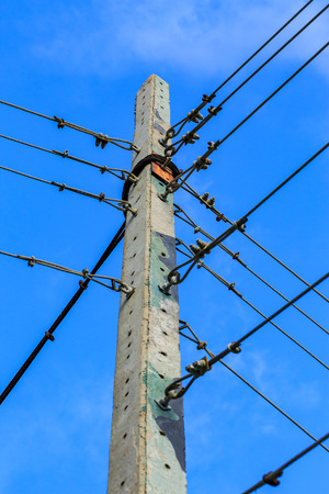 voltage gray: electricity post against blue sky