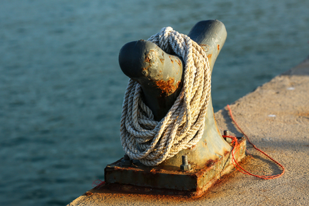 cleat: Rope and a jetty cleat with sunlight Stock Photo