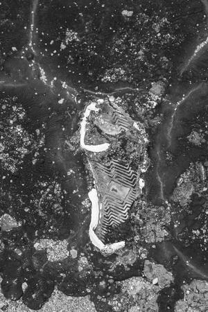 cement floor: damaged shoes in waste asphalt