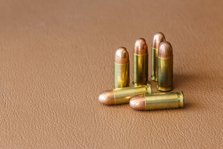 9mm ammo: Six bullets on brown leather