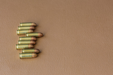 9mm ammo: Nine bullets on brown leather