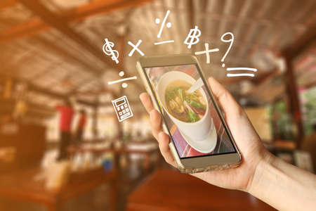 yum: Woman Hand holding smartphone with Geometry symbol in the restaurant for order some food
