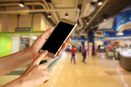 cell phones: woman hand holding and touch screen of smartphone,tablet,cell phone over shopping center Stock Photo