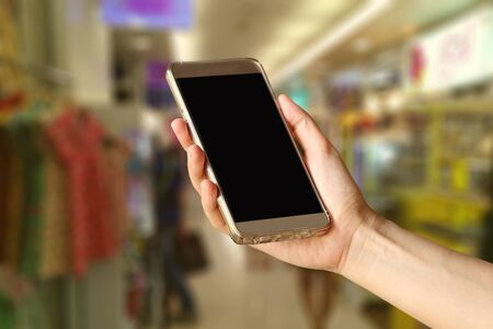 smartphone hand: Woman Hand holding smartphone at shopping center