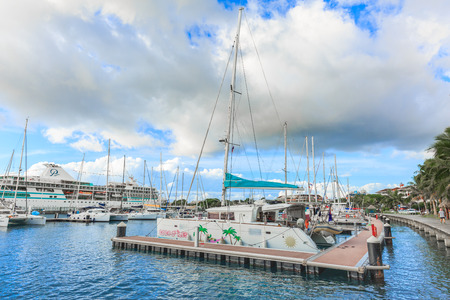 PAPEETE, FRENCH POLYNESIA – JULY 1, 2016 :  The sailing boat park in sunset time at Large seaport in Tahiti PAPEETE, FRENCH POLYNESIA on July 1, 2016 Editorial