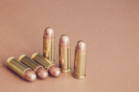 gunfire: Six bullets on brown leather
