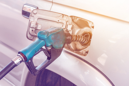 Closeup of pumping gasoline fuel into car tank with light effect
