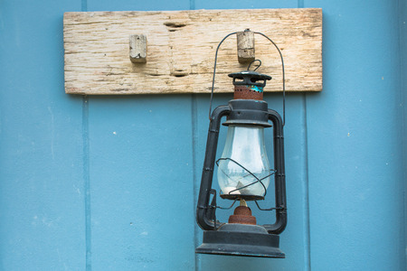 outmoded: Burning kerosene lamp hang on the wooden wall