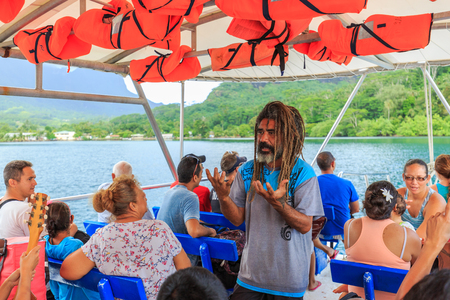 tahitian: PAPEETE, FRENCH POLYNESIA - OCTOBER 28, 2016 : Tahitian instructor guiding tourists on boat in the beautiful sea, Moorae Island at Tahiti PAPEETE, FRENCH POLYNESIA