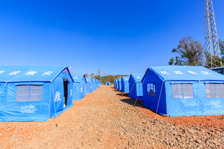 KUNMING, CHINA - NOVEMBER 26, 2016 : Tent Shelter With Temporary Beds Ready for Natural Disaster Victims and guards at Kunming, Yunnan province, China