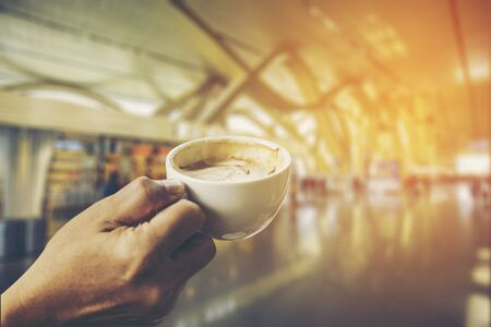 cup of coffee in the hands at blurred airport background Stock Photo