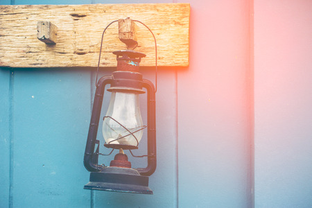 the outmoded: Burning kerosene lamp hang on the wooden wall