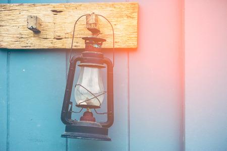 scintillating: Burning kerosene lamp hang on the wooden wall