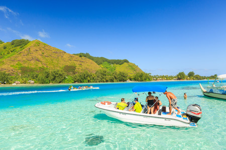 stingrays: PAPEETE, FRENCH POLYNESIA - MAY 11, 2017: The Tourists stay on speedboat after swimming and feeding Sharks and Stingrays in beautiful sea at Moorea Island, Tahiti PAPEETE, FRENCH POLYNESIA
