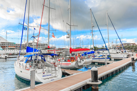 PAPEETE, FRENCH POLYNESIA - JUNE 28, 2017 : The sailing boat park in sunset time at Large seaport in Tahiti PAPEETE, FRENCH POLYNESIA.