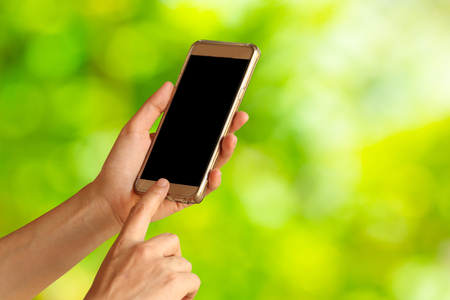 woman hand hold and touch screen smart phone,tablet,cellphone on green nature background Stock Photo