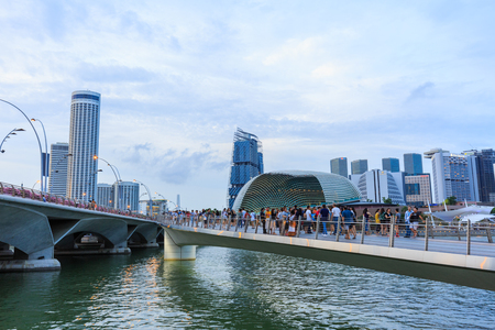 SINGAPORE – NOVEMBER 22, 2017 : View of multi ethnic people walking and taking picture on Jubilee Bridge a path to nearby Esplanade Theatres on the Bay