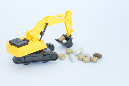 Selective focus of  Backhoe and pills , on white background Stock Photo