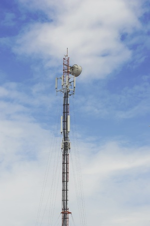 Red and White Telecommunication tower with blue sky and cloud background photo