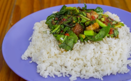 Kale with crispy pork rice on wood table photo