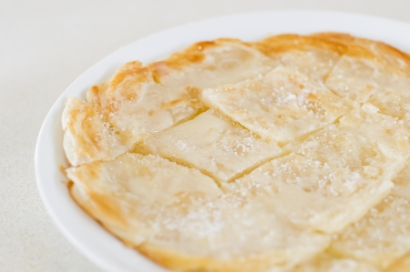 Roti Canai Pour Condensed milk and sprinkle sugar on top,cut into small pieces and place on a dish