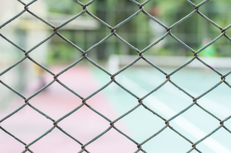 Metal mesh wire fence with tennis court photo