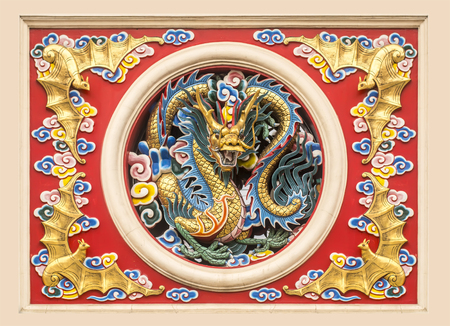 frame of statue Golden Chinese Dragon in circle and golden bat with colorful cloud on wall at Ancient chinese temple,thailand photo