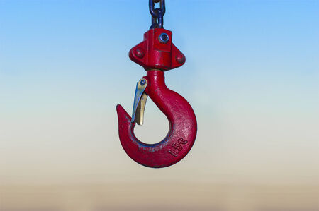 red Industrial hook hanging on reel chain and blue sky sunset background photo