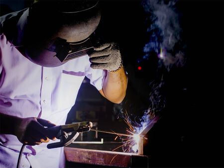 voltaic: welder working with protective mask welding metal and sparks