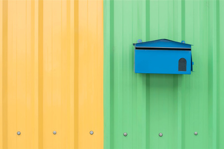 blue mail box on orange and green corrugated metal sheet as background photo