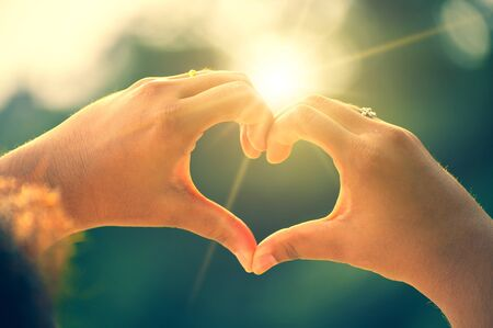The hands of women and men are the heart shape with the sun light passing through the hands