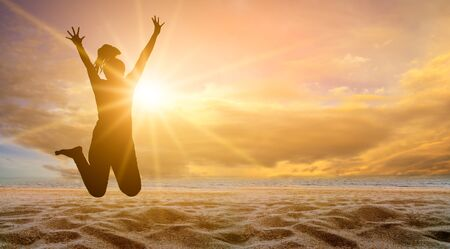 The girl is jumping with fun on the beach, the sea with the golden sun in the evening. summer concept