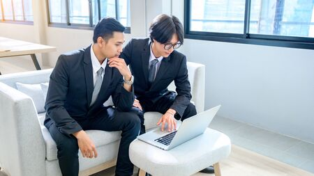 A group of 2 male business men are working with computers seriously in the office.