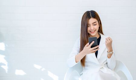 Business women wear white clothes glad to play mobile phone in a white background