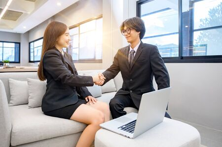 Business people shaking hands on a desk with a computer in the back