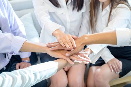 A group of business people lay hands together for unity in the work team Banco de Imagens